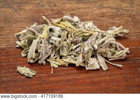loose leaves of dry sage herb tea, a pile on a rustic weathered wood