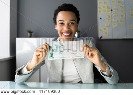 African American Women Holding Payroll Cheque Or Money Check