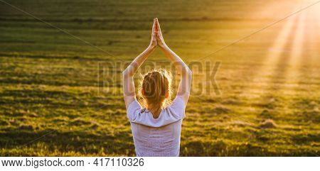 woman in a balancing pose at sunset yoga outdoors