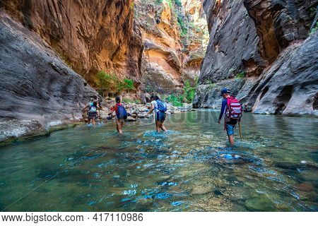 Group of diverse people hiking through a river at Zion National Park. Exploring the beauty of the Narrows and the beautiful canyons of the narrows
