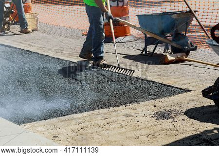 Construction Site Is Worker Laying New Asphalt Road On Rolling Fresh Hot Asphalt
