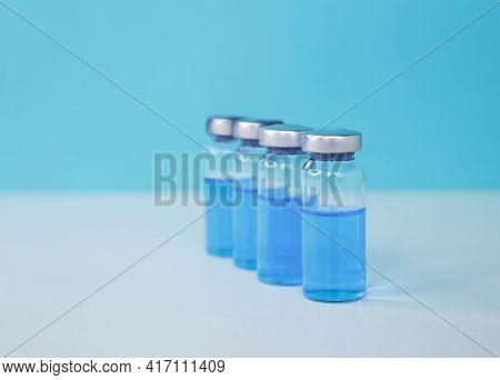 Coronavirus Vaccine Vials In A Row. Medical Injection. Medicine Vial Or Flu, Measles Vaccine Bottle