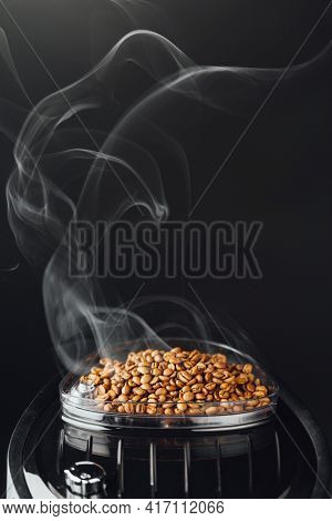 fresh roasted coffee beans with smoke in coffeemaker bean container, close-up view