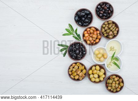 Different Kinds Of Olives And Olive Oil In A Clay And White Bowls With Olive Leaves Flat Lay On A Wh