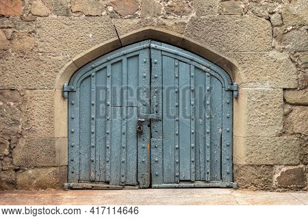 Ancient Stone Wall With A Gate In The Old Castle. Wooden Gate Of A Medieval Castle