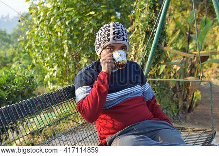 Healthy Indian Man Drinking Tea In Morning At The Park . Traveling Man Enjoying Tea In Darjeeling, I