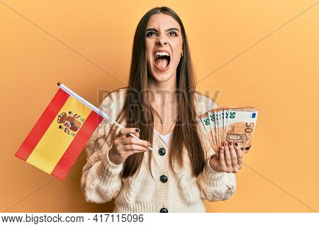 Beautiful brunette young woman holding spain flag and euros banknotes angry and mad screaming frustrated and furious, shouting with anger looking up.