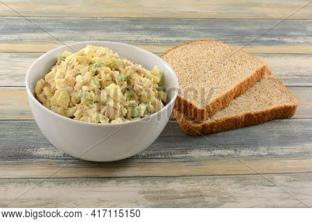 Albacore Tuna Salad With Chopped Apple And Avocado In White Bowl Next To Two Whole Wheat Bead Slices
