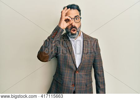Middle age man with beard and grey hair wearing business jacket and glasses doing ok gesture shocked with surprised face, eye looking through fingers. unbelieving expression.