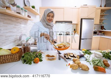 Woman With Hijab Cooking In Her House Kitchen For Dinner