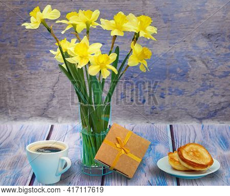 Bouquet Of Yellow Daffodils In A Glass Vase, A Gift Box, A Cup Of Coffee And A Plate With Pancakes O