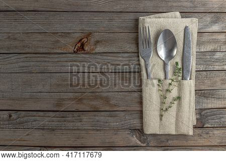 Rustic Table Setting In Natural Warm Colors. Plate And Cutlery With Linen Napkin Over Wooden Backgro
