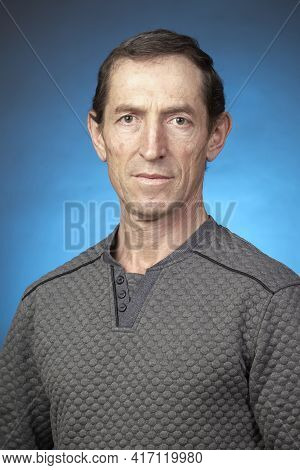 Portrait Of An Ordinary Elderly Man On A Blue Background.