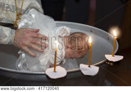 Orthodox Rite Of Baptism Of A Child. The Hands Of The Priest Bathe The Baby In The Baptismal Bath.