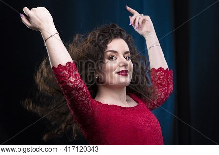 A Beautiful Brunette Girl In A Red Dress Threw Up Her Curly Hair.