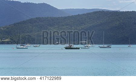 Airlie Beach, Queensland, Australia - April 2021: Boats Anchored Off Shore In A Bay Of Water With Hi