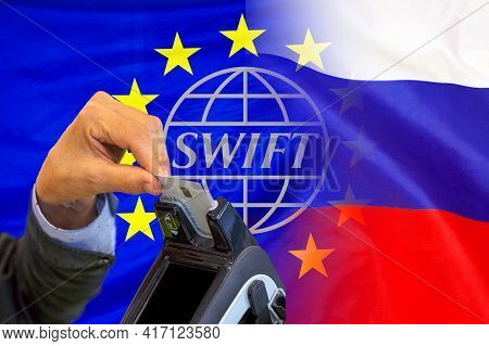 Flag Of Eu And Russia Flag And Text Of Swift. Hand Of Woman With Credit Card In Payment Terminal. So