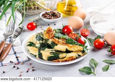 Omelet With Spinach Leaves. Omelette On Plate, Scrambled Eggs On A Light Slate, Stone Or Concrete Ba
