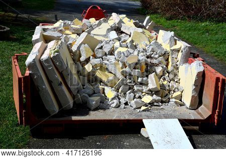 Red Container Full Of Rubble From The Reconstruction Of The Apartment. The Bricks And Concrete Truck