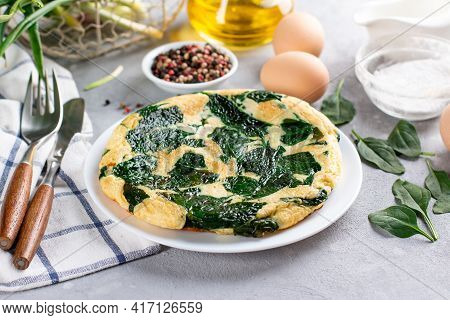 Frittata Made Of Eggs, Cheese And Spinach Omelet. Frittata - Italian Omelet On A White Plate On A Gr