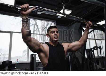 Attractive Muscular Bodybuilder Working Out On Lat Pulldown Gym Machine