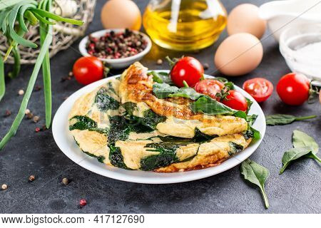 Omelet With Spinach Leaves. Omelette On Plate, Scrambled Eggs On A Dark Slate, Stone Or Concrete Bac