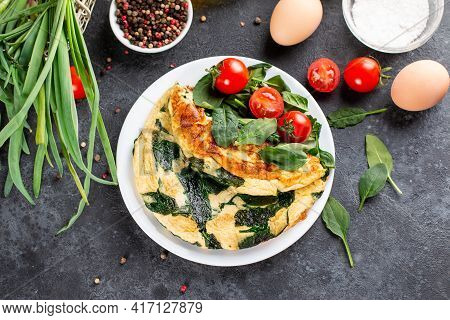 Green Omelet With Spinach, Tomato And Spices On Plate. Frittata - Italian Omelet. Top View.