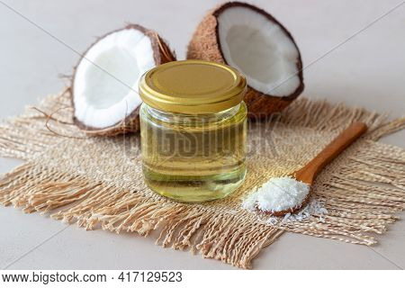 Coconut Oil In A Jar And Fresh Coconuts On A Beige Background. Natural Cosmetics.