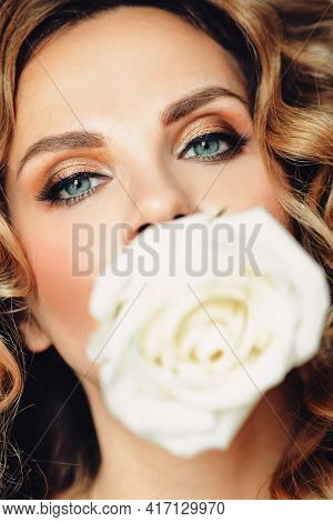 Gorgeous Woman With Rosebud In Closeup Holding A Fragile White Rose Bud And Looking At Camera In Clo