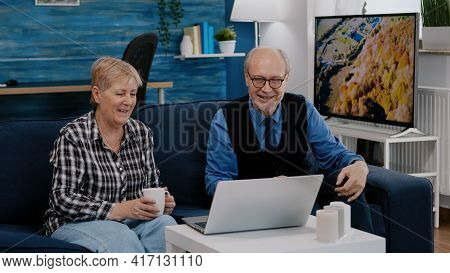Enthusiastic Couple Of Pensioners Sitting Together On Sofa Talking On Video Call