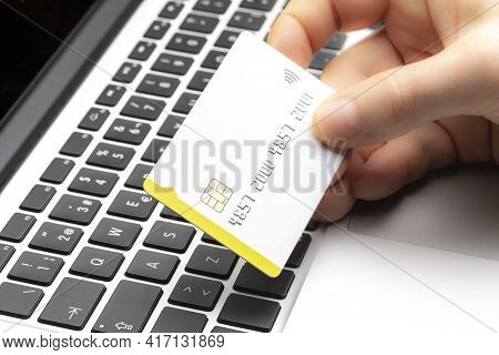 Close-up Of Online Shopper Paying With Credit Card On Computer Keyboard With Copy Space. Online Shop