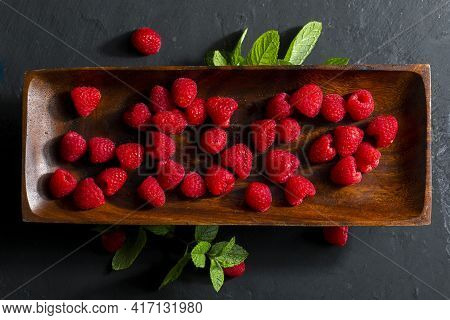 Delicious And Appetizing Raspberries On An Ebony Wood Tray And Spearmint (peppermint, Mint) Leaves.