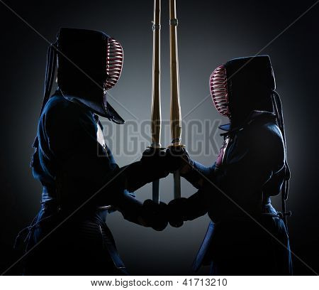 Two kendoka opposite each other with wooden sword. Japanese martial art of sword fighting