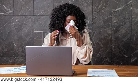 Tired Afro-american Company Worker Lady With Curly Hair Sneezes Into Paper Napkin And Puts Palm On F