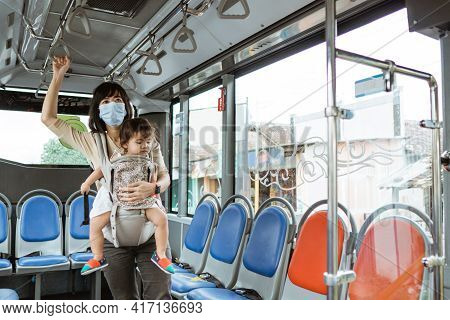 An Asian Mother Wears A Mask And Carries Her Child While Standing Holding On To The Bus