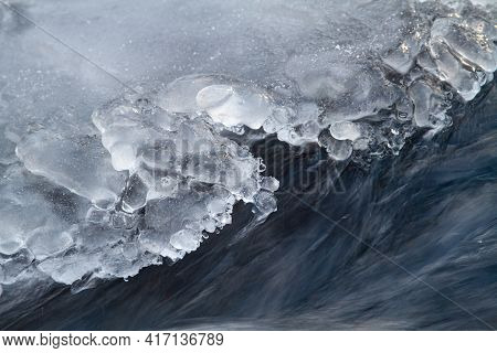 River Water Flows Quickly Along The Edge Of The Shore Ice. The Edge Of The Ice Is Treated With Water