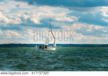 Sailing Yacht In The Lake With Gloomy Sky Before The Rain And Windy Weather. Yacht Sailing On The La