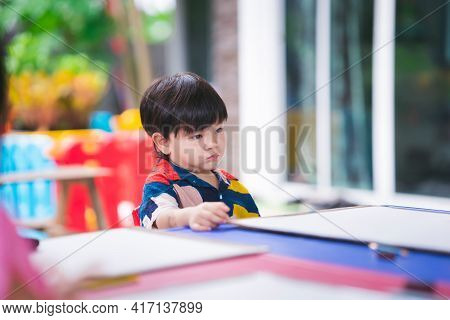 Asian Boy Make Bored Face Sitting On Chair. Baby Wait To Learn Art Paint. Child Is Annoyed Because O