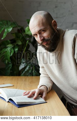 White Bald Man 35 Years Old With A Beard And Mustache In A Beige Jumper With A Book At The Table