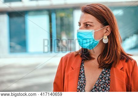 Young Woman With A Foxy Hair Wearing Protection Face Mask Against Coronavirus Mers-cov, Novel Corona