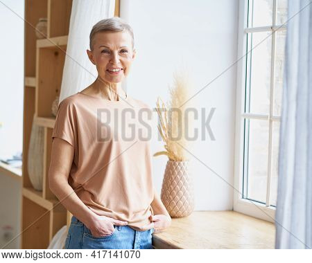 Portrait Of Attractive Happy Middle Aged Woman In Casual Wear Keeping Hands In Jeans Pockets And Smi