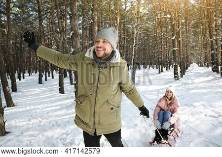 Man Pulling His Girlfriend In Sleigh Outdoors On Winter Day
