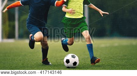 Football Soccer Player In A Duel In Rain. Young Footballers Duel With Ball