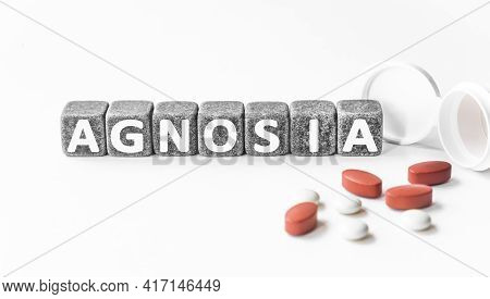 Word Agnosia Is Made Of Stone Cubes On A White Background With Pills. Medical Concept Of Treatment,