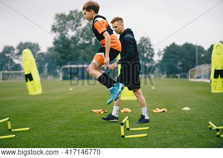 Young Man Jumping Over Practice Hurdles In Soccer Training. Soccer Coach Watching Boy On Training. P