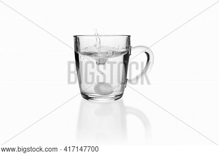 Soluble Fizzy Tablet Fallen With Splash To Transparent Glass Mug On White Background.