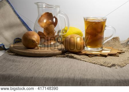 On A Jute Napkin, On A Stand, There Is A Cup With Brewed Onion Peels And Lemon. Nearby Is A Jug For
