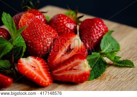 Appetizing Juicy Bright Strawberries On A Kitchen Wood Board On A Black Background With Branches Of