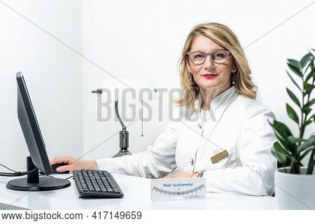 Blonde Female Physician Doctor Standing In Her Office With Pedi-scoliometer On A Table. Portrait Of