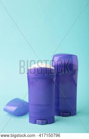 Violet Antiperspirant Deodorant On Blue Background. Skin Care Concept. Copy Space, Top View. Vertica